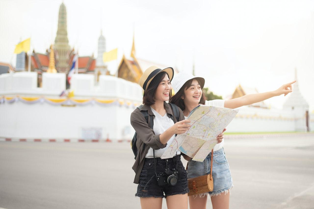 women tourists holding map