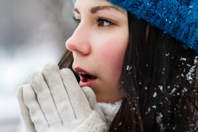 woman warming up hands with breath