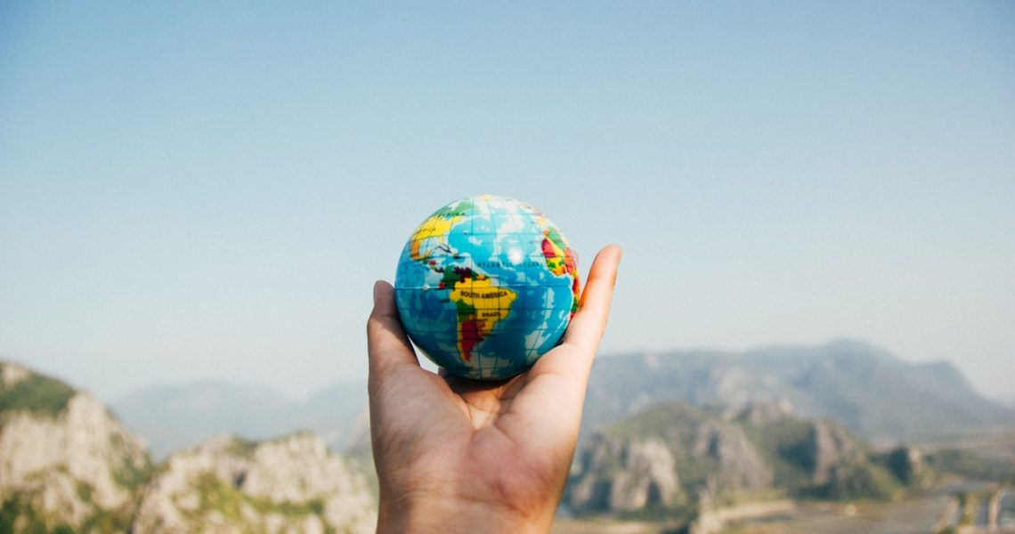 person holding a globe up